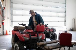 Male farmer refueling quad bike in barnの写真素材 [FYI02334023]