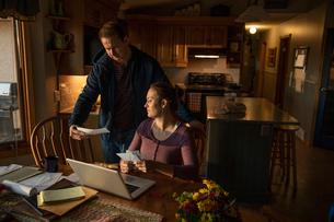 Couple paying bills at laptop in kitchenの写真素材 [FYI02334037]