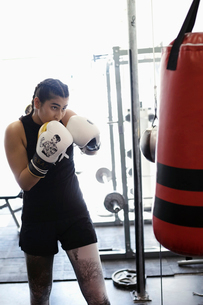 Tough female boxer training at punching bag in gymの写真素材 [FYI02334040]