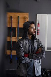 Portrait male boxer in hoody looking away in gymの写真素材 [FYI02334045]