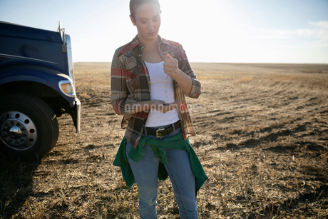 Female farmer examining soil on sunny farmの写真素材 [FYI02334056]