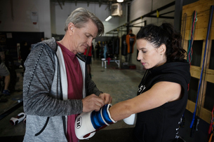 Trainer helping female boxer putting on boxing gloves in gymの写真素材 [FYI02334069]