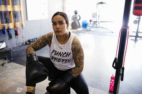 Portrait confident, tough female boxer resting in gymの写真素材 [FYI02334076]