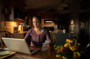 Woman paying bills at laptop in kitchenの写真素材 [FYI02334078]