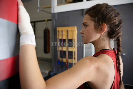 Tough female boxer at punch bag in gymの写真素材 [FYI02334082]