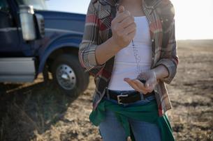 Female farmer examining soil on farmの写真素材 [FYI02334084]