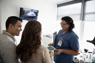 Female nurse showing ultrasound image to pregnant couple in clinic examination roomの写真素材 [FYI02334145]