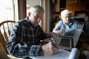 Senior couple paying bills at laptop in kitchenの写真素材 [FYI02334165]