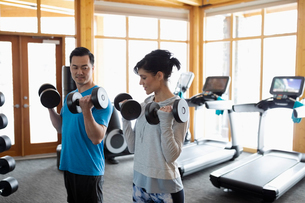 Personal trainer and client doing dumbbell biceps curls in gymの写真素材 [FYI02334175]