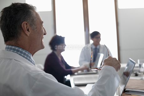 Smiling male doctor listening in conference room meetingの写真素材 [FYI02334176]