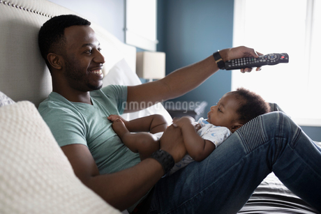 Smiling father with remote control watching TV with baby son in lap on bedの写真素材 [FYI02334212]