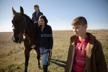 Mother and sons with horse in sunny fieldの写真素材 [FYI02334240]