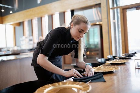 Waitress folding napkins, setting restaurant tableの写真素材 [FYI02334254]