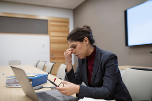 Tired businesswoman at laptop in conference roomの写真素材 [FYI02334267]