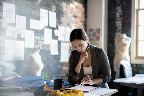 Focused female fashion designer using digital tablet in officeの写真素材 [FYI02334280]