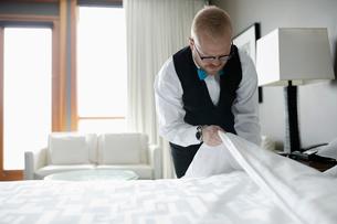 Dedicated male room service hotel staff housekeeper making bed in hotel roomの写真素材 [FYI02334289]