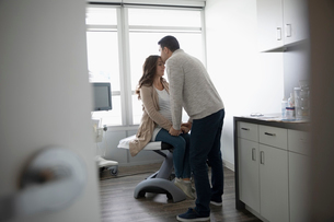 Affectionate, loving husband kissing forehead of pregnant wife in clinic examination roomの写真素材 [FYI02334322]