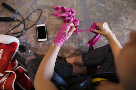 Female boxer wrapping wrists with pink tapeの写真素材 [FYI02334323]