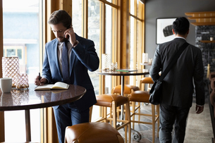 Businessman talking on cell phone and writing in notebook at table in loungeの写真素材 [FYI02334328]