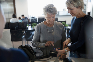 Woman helping senior mother pay at clinic check-inの写真素材 [FYI02334351]