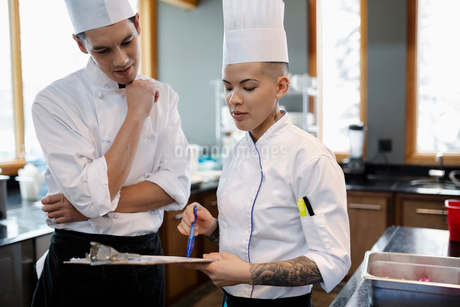 Executive and sous chef planning in restaurant kitchenの写真素材 [FYI02334352]