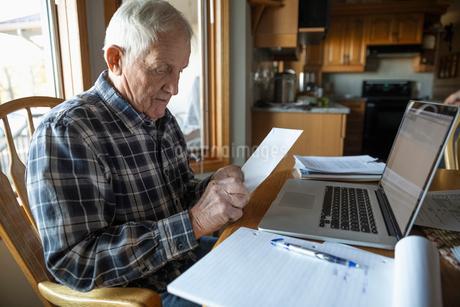 Senior man paying bills at laptop in kitchenの写真素材 [FYI02334357]