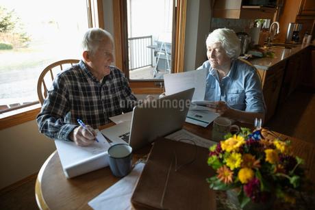 Senior couple paying bills at laptop in kitchenの写真素材 [FYI02334364]