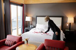Female room service hotel staff arranging rose petals on luxury hotel room bedの写真素材 [FYI02334386]