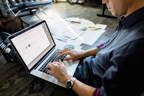 Creative businessman working at laptop on office floorの写真素材 [FYI02334392]
