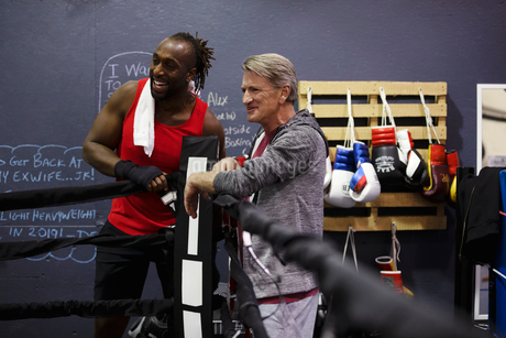 Male boxer and trainer talking in gymの写真素材 [FYI02334410]