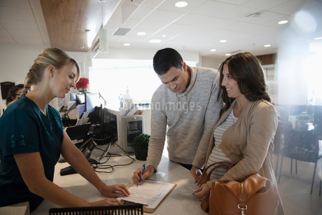 Pregnant couple checking in and filling out paperwork at clinicの写真素材 [FYI02334436]