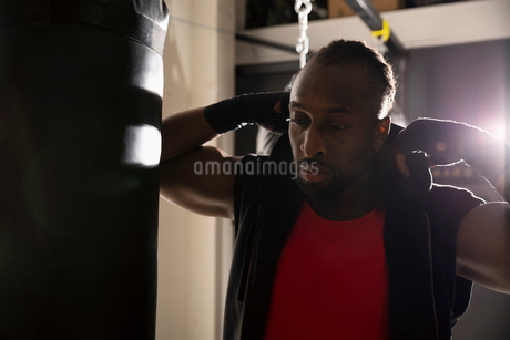Male boxer at punching bag in gymの写真素材 [FYI02334460]