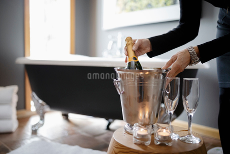 Room service hotel staff preparing candlelight champagne bath in luxury hotel bathroomの写真素材 [FYI02334475]