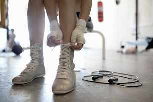 Close up female boxer tying shoes in gymの写真素材 [FYI02334481]