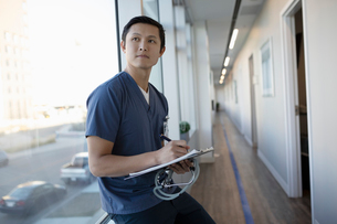 Thoughtful male nurse with clipboard in clinic corridorの写真素材 [FYI02334540]