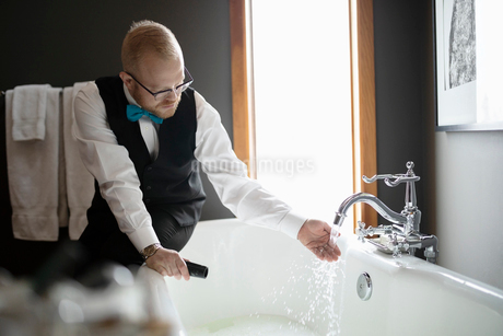 Male room service hotel staff preparing bath in hotel roomの写真素材 [FYI02334579]