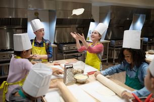 Girl tossing pizza dough in cooking classの写真素材 [FYI02334631]