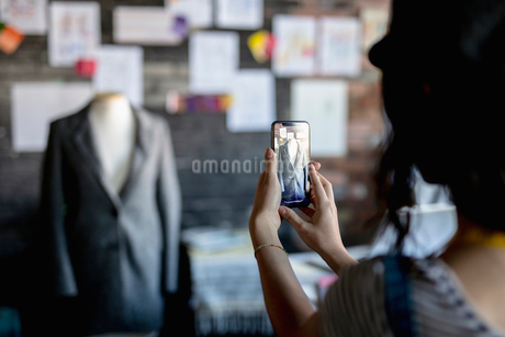 Female fashion designer with camera phone photographing coat on dressmakers model in officeの写真素材 [FYI02334642]