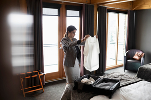 Businesswoman unpacking suitcase in hotel roomの写真素材 [FYI02334645]