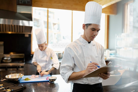Executive chef and prep cook cooking and planning in restaurant kitchenの写真素材 [FYI02334650]