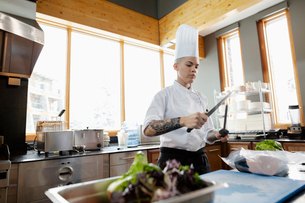 Female chef with tattoos sharpening knife in restaurant kitchenの写真素材 [FYI02334669]