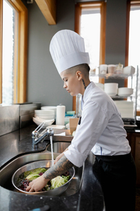 Female prep cook washing vegetables in restaurant kitchenの写真素材 [FYI02334672]