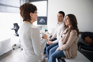 Female obstetrician talking with pregnant couple in clinic examination roomの写真素材 [FYI02334673]