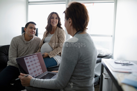 Female obstetrician with laptop talking with pregnant couple in in clinic examination roomの写真素材 [FYI02334696]