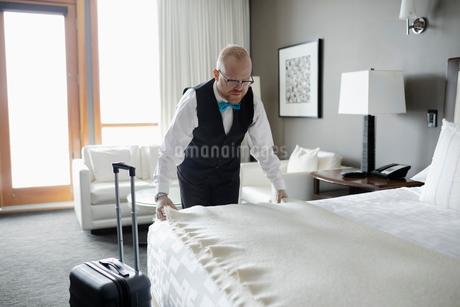 Male room service hotel staff straightening blanket on bed in luxury hotel roomの写真素材 [FYI02334704]