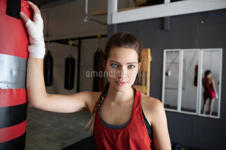 Portrait confident, tough female boxer at punching bag in gymの写真素材 [FYI02334716]