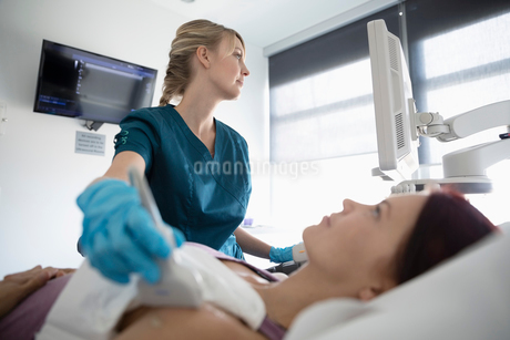 Female technician performing ultrasound soft tissue imaging on shoulder of woman in clinic examinatiの写真素材 [FYI02334732]