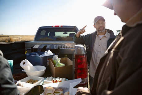 Male farmers talking and eating lunch, taking a break on sunny farmの写真素材 [FYI02334736]