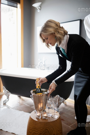 Female room service hotel staff preparing champagne bath in hotel bathroomの写真素材 [FYI02334741]