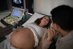Affectionate pregnant couple holding hands, receiving ultrasound in clinic examination roomの写真素材 [FYI02334747]